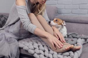 Eine Frau mit Kompressionsstrümpfen und ein freundlicher Hund